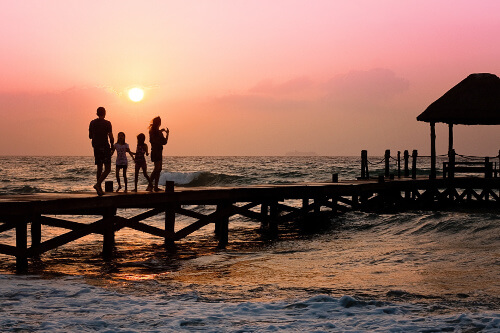 family on pier with sunset