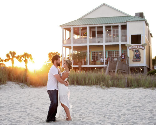 man and woman on beach by house